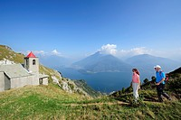 Two hikers near San Bernardo chapel, Monti Lariani, Lake Como in background, Lombardy, Italy