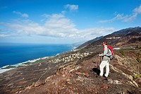 Hiker at volcano crater looking at the sea, Volcano San Antonio, Fuencaliente, La Palma, Canary Islands, Spain, Europe