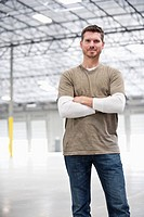 Caucasian man standing in empty warehouse