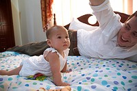 Father playing with baby girl on bed