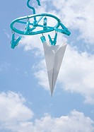 Paper plane hung out on clothesline