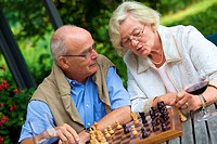 Senior couple on terrace playing chess