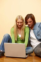 Young couple using laptop on floor