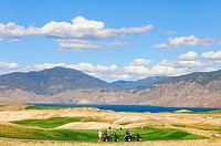 Golfers and golf carts at the Tobiano Golf Course and Kamloops Lake near Kamloops, British Columbia, Canada.