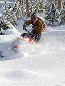 A solo snowmobiler makes his way down unchartered powder in the Monashee Mountains, in the North Thompson region near Valemount, British Columbia, Can...