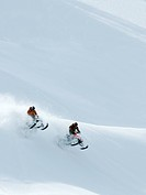 A pair of snowmobilers jump off a ridge on a stunning day in the Monashee mountains, North Thompson region near Valemount, British Columbia, Canada