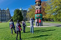 Asian tourists posing in front of totem pole on the British Columbia Legislative Building grounds, Victoria, British Columbia, Canada