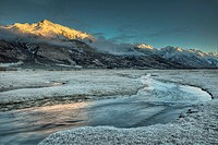 Dawn light on Ben Ohau range near Glentanner Station, frosted grass on Tasman river flats, edge of Aoraki / Mt Cook National park, New Zealand.