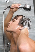 Close_up of man taking shower in bathroom