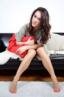 young woman sitting with cushion on sofa