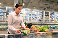 Young woman in the supermarket buys food and fruits