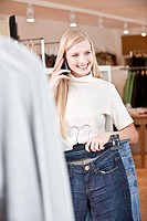 Young woman talking on a mobile phone in a clothes shop