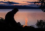 Mann sitzt abends am Lagerfeuer whrend einer Trekkingtour in Femunden, Norwegen
