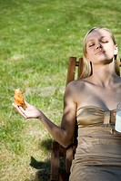 Woman eating breakfast in the park.