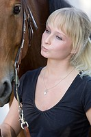 blonde woman with her own brown horse