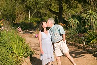 Middle_aged husband walks down springtime path with his pregnant wife in gardens in Ojai, California