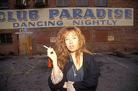 Female smoking in night club parking lot, Los Angeles, California