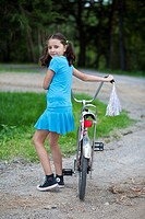 Young girl with bike in the country