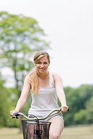 Portrait of a blonde woman riding a bike in the park