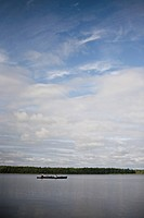 Two kayakers relax on a northern lake under cloudy skies.