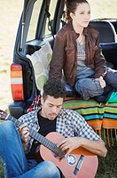 couple sitting in the back of a jeep, he plays guitar as she looks out into the distance