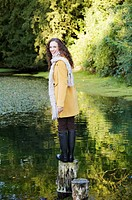 woman, laughing while standing on wooden log on a lake. She is wearing wellington boots.