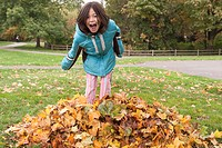 Young girl in a pile of fallen leaves