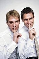 Two businessmen with finger on lips, smiling