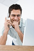 Young businessman talking on the phone, smiling