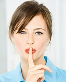 Young woman with finger on lips, close_up