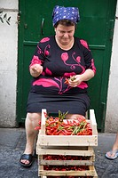 A woman sorting vegetables in front of green door in Amalfi, a town in the province of Salerno, in the region of Campania, Italy, on the Gulf of Saler...