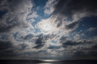 Sun behind clouds above the ocean
