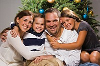 Parents with children sitting at Christmas tree