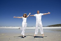 Mature couple jumping on the beach