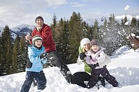 Family having snowball fight on hill, smiling
