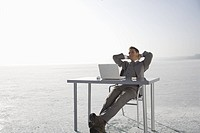 Mid adult man businessman relaxing at laptop on ice