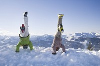 Young girl and boy performing handstands in snow