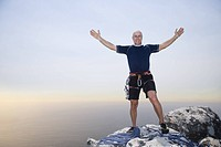 Portrait of mature man with arms out on mountain summit, front view