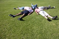 Mature men lying on backs on golf course