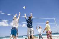 Mature men leaping for volley ball on beach, rear view