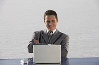 Mid adult business man smiling at laptop on desk on ice