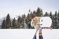 Young woman making snowman, smiling