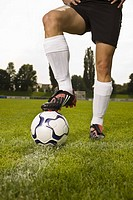 Man in soccer uniform standing with soccer ball on grass