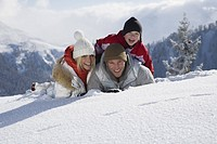 Portrait of family lying in snow, smiling
