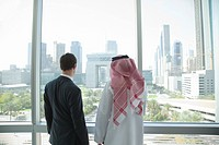 Western and middle eastern businessmen by window of dubai office