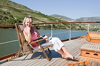 Mature reading book woman on a boat holiday