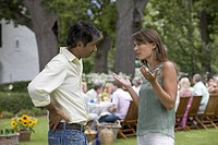 A couple having an argument at a summer party