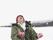 A man wearing a red woolen hat and gloves watching the snow fall