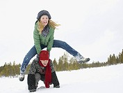 A young couple playing leap frog in the snow