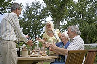 A group of senior friends sitting outdoors enjoying a bottle of wine together